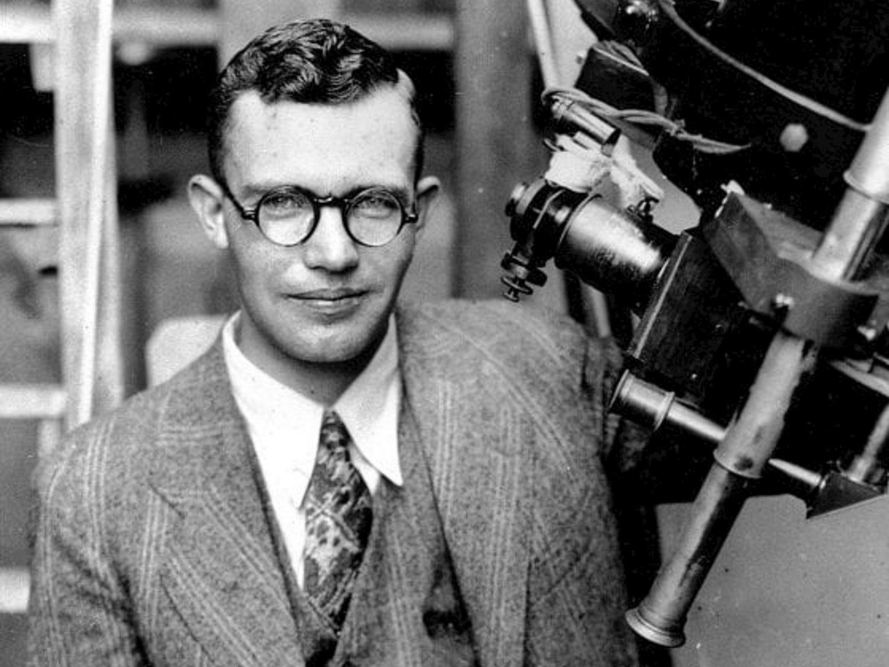 Clyde Tombaugh poses with the telescope through which he discovered the Pluto