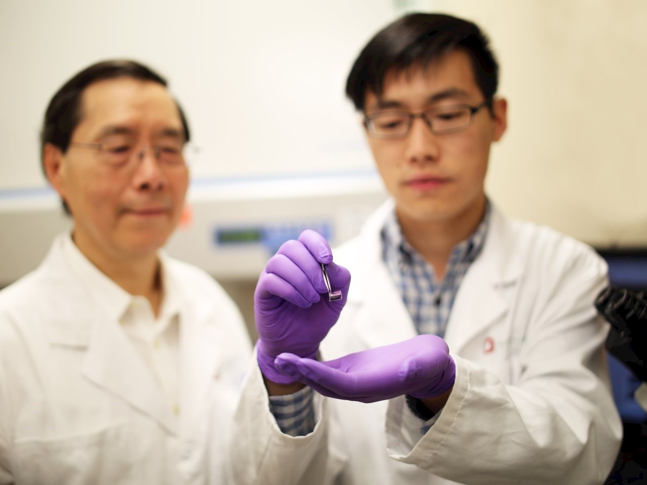 James Lee, PhD, left, examines a silicon chip with Junfeng Shi