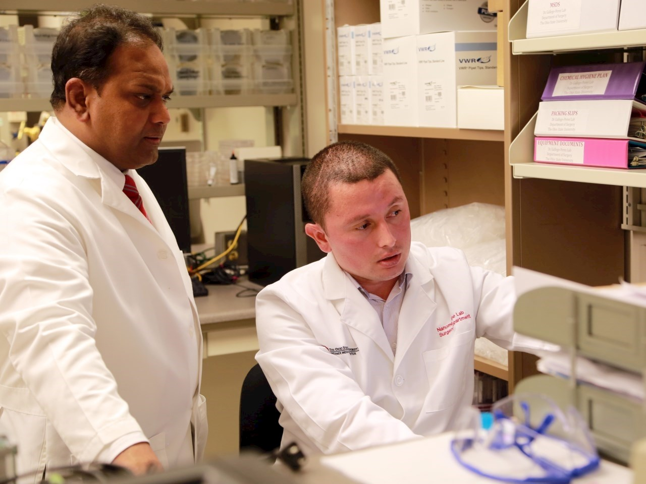 Chandan Sen, PhD, left, looks at study data with Daniel Gallego-Perez