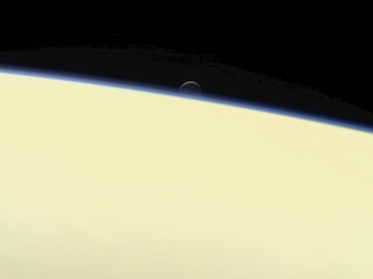 Enceladus setting behind Saturn