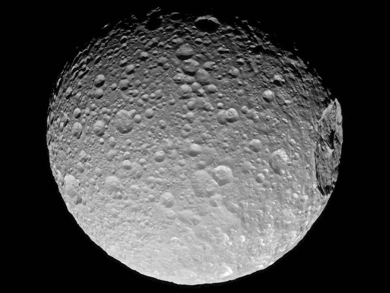Mimas' gigantic crater Herschel lies near the moon's limb in this Cassini view